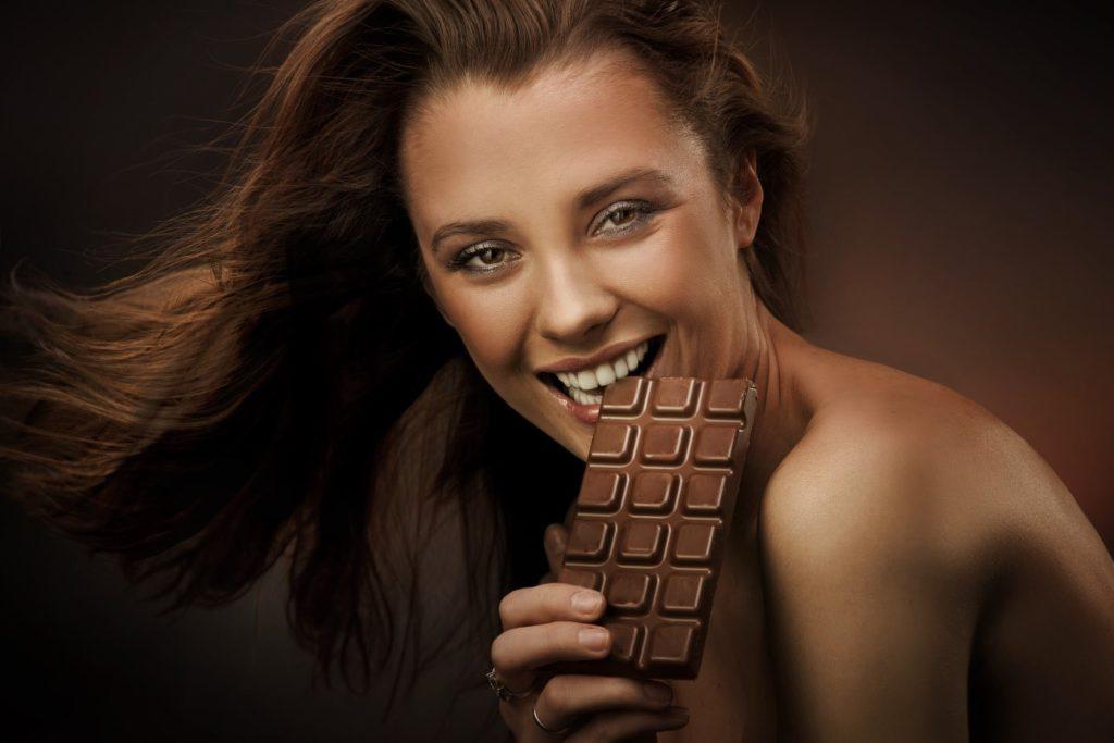 Jeune femme sourit de toutes ses dents en croquant du chocolat.