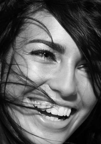 Portrait femme brune souriante après un traitement d'esthétique dentaire.