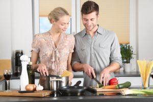 Couple cuisinant ensemble dans la joie et la bonne humeur.