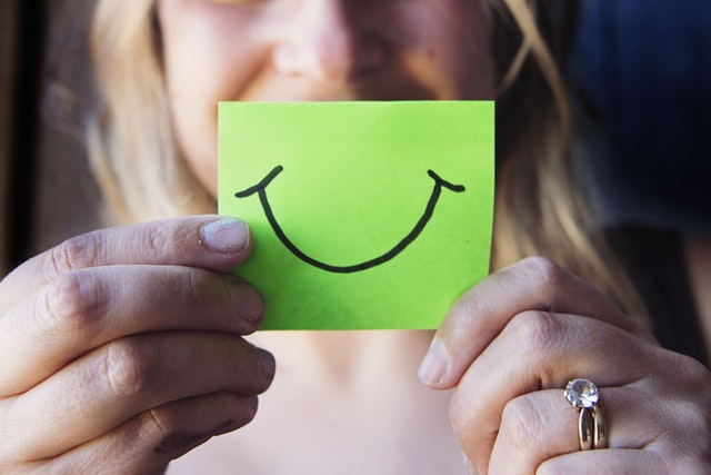 Photo d'une femme tenant un post-it devant son sourire.