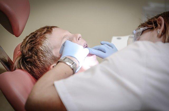 Dentiste travaillant dans la bouche d'un enfant.