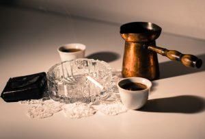 Cigarette et tasse de café sur une table.
