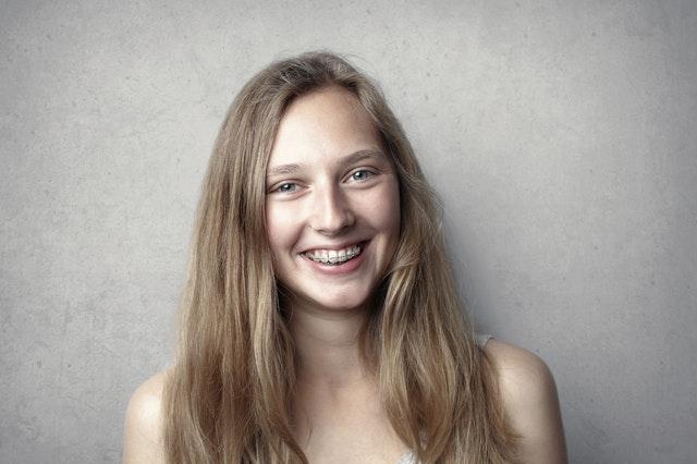 Femme souriante portant un appareil dentaire.